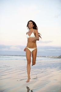 Woman in bikini running in wet sand on beach