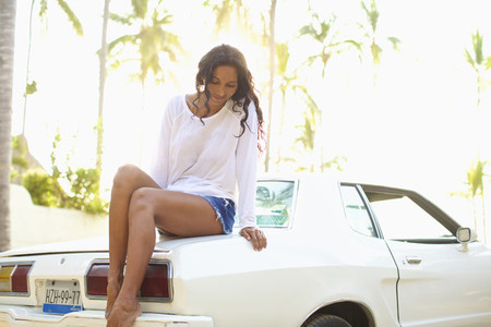 Woman in shorts sitting on car