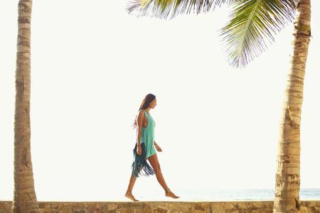 Woman walking along sunny ocean ledge