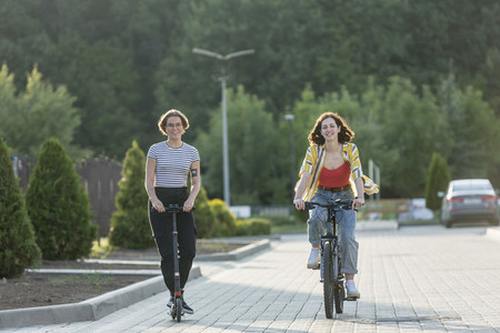 Women friends riding bicycle and push scooter on road