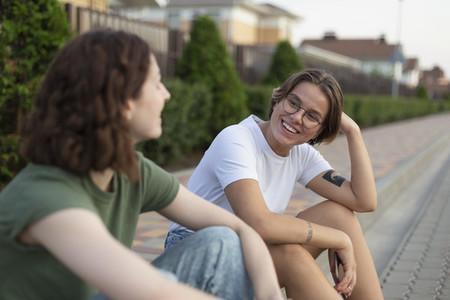 Women friends talking on neighborhood curb