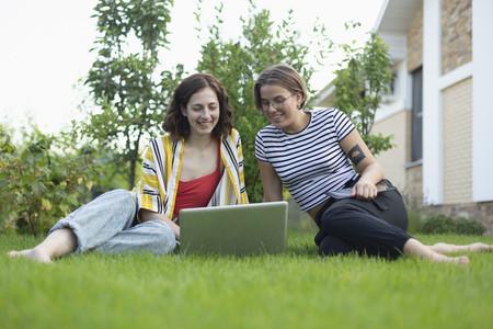 Women friends using laptop in grass