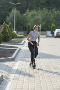Young woman riding push scooter on sunny road