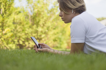 Young woman with headphones using smart phone in grass