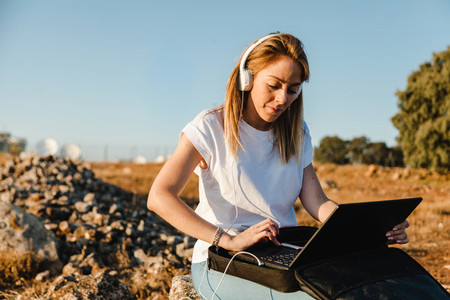 Young woman with her laptop communicates with antennas