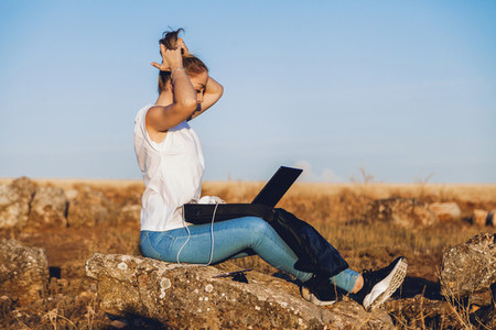 girl with laptop and headphones combs her hair in the field