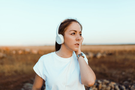 Young woman with her headphones listened external communications