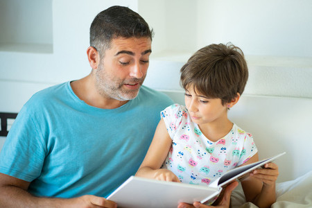 Middle age father with her eight years daughter using digital tablet in bedroom