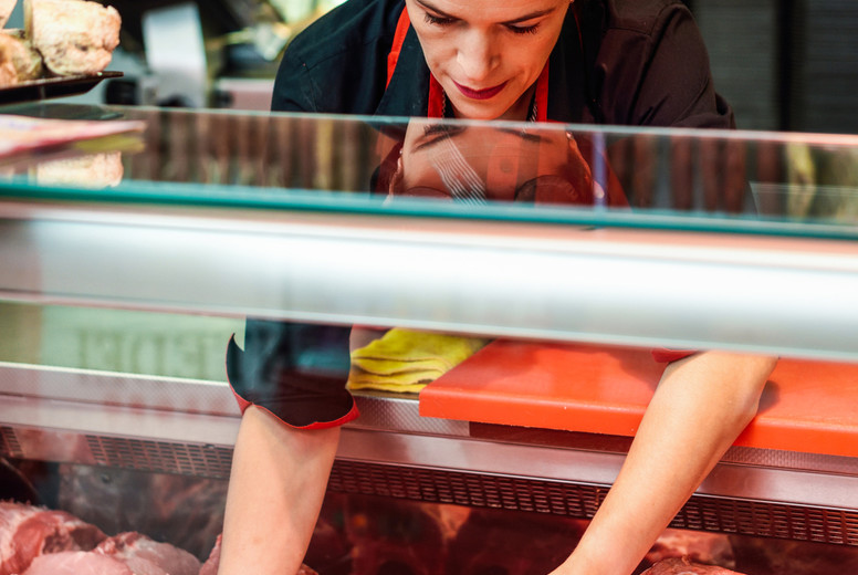 Butchers hands holding meat piece in shop