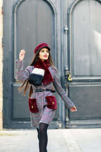 Happy beautiful girl with very long hair wearing winter coat and cap outdoors