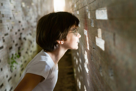 Child looking through the bricks inside the Nazari Wall