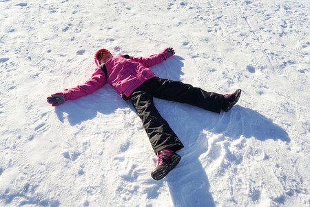 Little girl making a snowangel wearing snow clothes