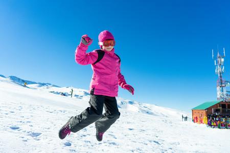 Little girl jumping on the snow at Sierra Nevada ski resort