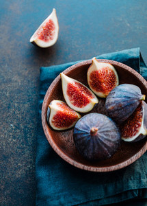 Macro photo of ripe figs in a wooden small bowl on a table