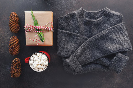 Top view of Christmas or winter time flat lay with hot chocolate  gift box and a woolen sweater on a dark background