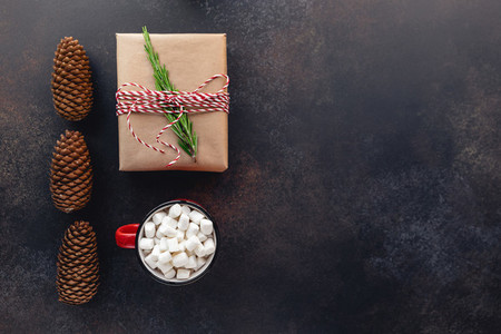 Top view of Christmas or winter time flat lay with hot chocolate  gift box on a dark background with copy space