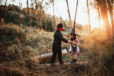Two children disguised for Halloween in the woods