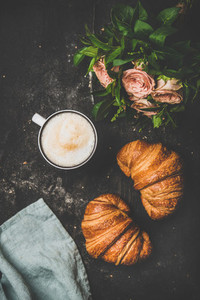 Cup of cappuccino  fresh croissants and flowers over shabby background