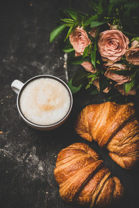 Cup of cappuccino  fresh croissants and pink flowers  top view