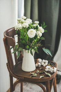 Spring white buttercup flowers in white enamel jug at home