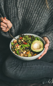 Woman sitting and eating healthy vegetarian dinner from Buddha bowl