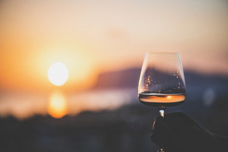 Mans hand holding glass of wine with sea at background
