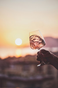 Glass of wine in hand with sunset at background