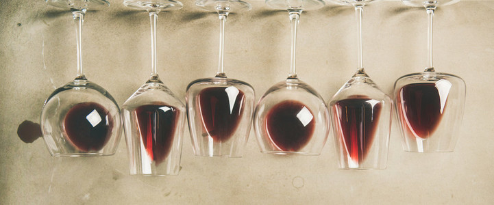 Red wine in different glasses over grey background