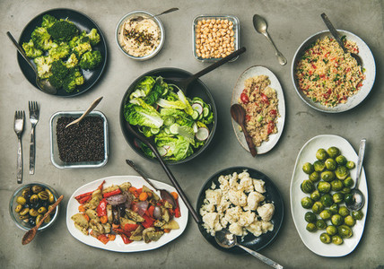Healthy vegetarian dishes in plates ans bowls on concrete table