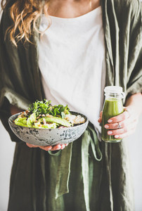 Woman holding healthy vegan superbowl and smoothie in hands