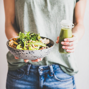 Woman in jeans holding healthy superbowl and smoothie  square crop