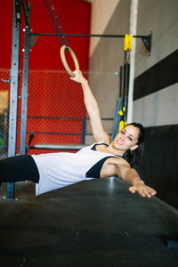 Beautiful muscular woman doing exercise with ring system