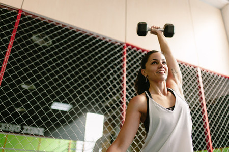 Fitness smiling woman lifting a dumbbell in the gym
