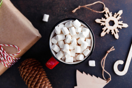 Hot chocolate in a red mug with marshmallow surrounded Christmas decoration