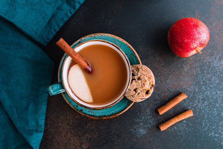 Wintertime chai spiced apple cider with assam tea  cinnamon  ginger  cardamom and almond milk  Christmas or Thanksgiving cozy flat lay