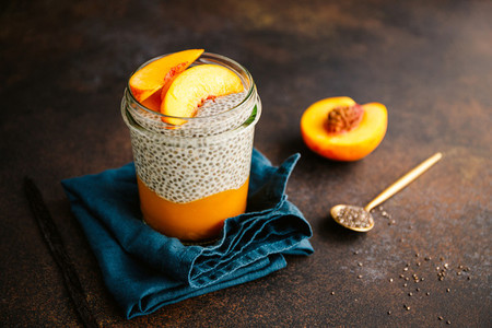 Portion healthy vegan chia pudding with almond milk  vanilla and peaches in a glass jar on a dark table