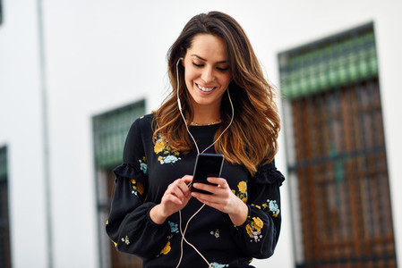 Woman listening to the music with earphones and smart phone outdoors