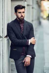 Young bearded man in urban background wearing british elegant suit in the street