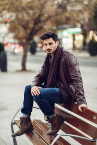 Thoughtful young man sitting on an urban bench