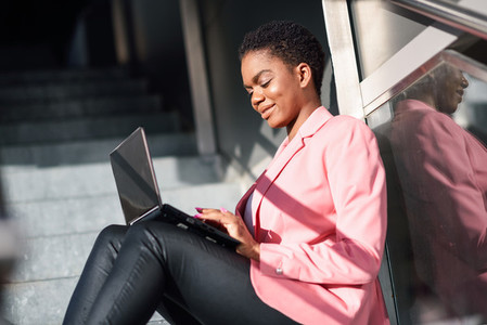 Smiling black businesswoman sitting on urban steps working with a laptop computer