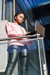 Black businesswoman standing near business office building working with a laptop computer