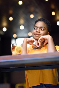 Young black woman with very short hair taking a glass of cold tea