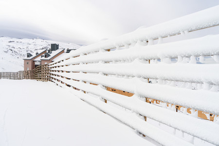 Winter mountains landscape with snowed fence in Sierra Nevada