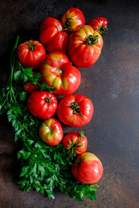 Top view of brandywine sort tomatoes with greens for seasonal canning or salad on a table