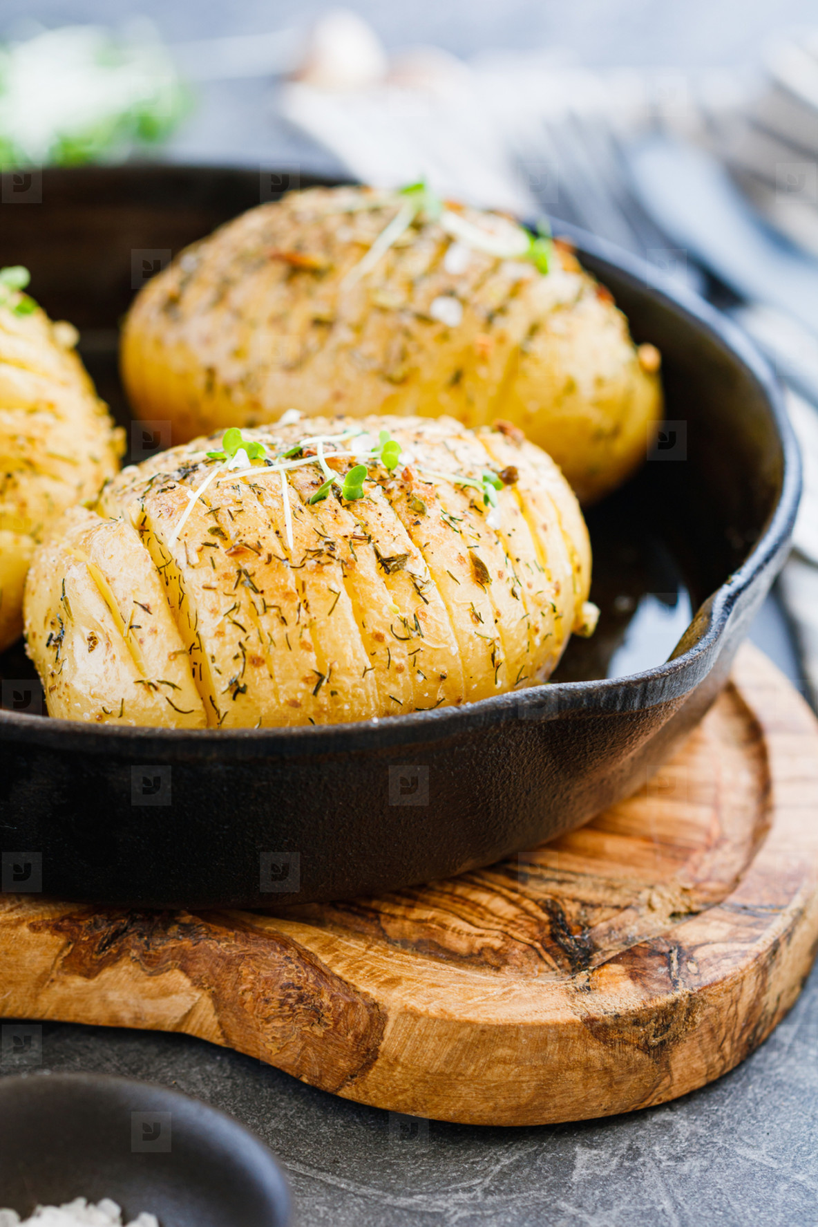 Close up of homemade baked potato with olive oil  garlic  rosemary  mustard  dill and black pepper in a cost fry pan