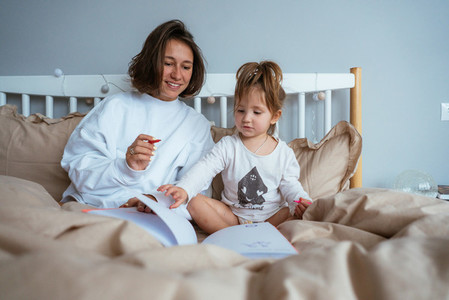 Mom and daughter draw in bed