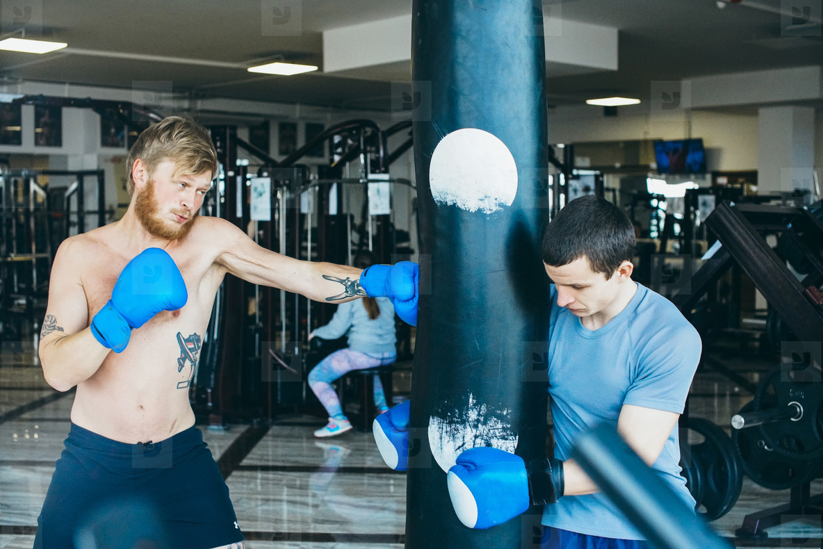 Boxer with punching bag in gym