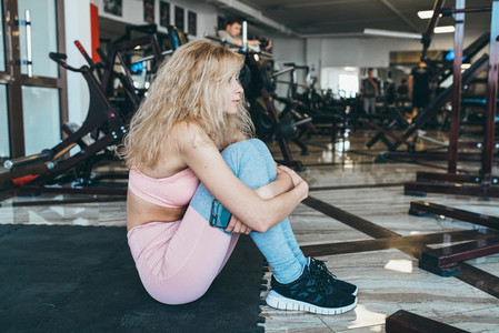 Girl sits on the floor in the gym