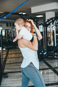 Young mother with her young son in the gym