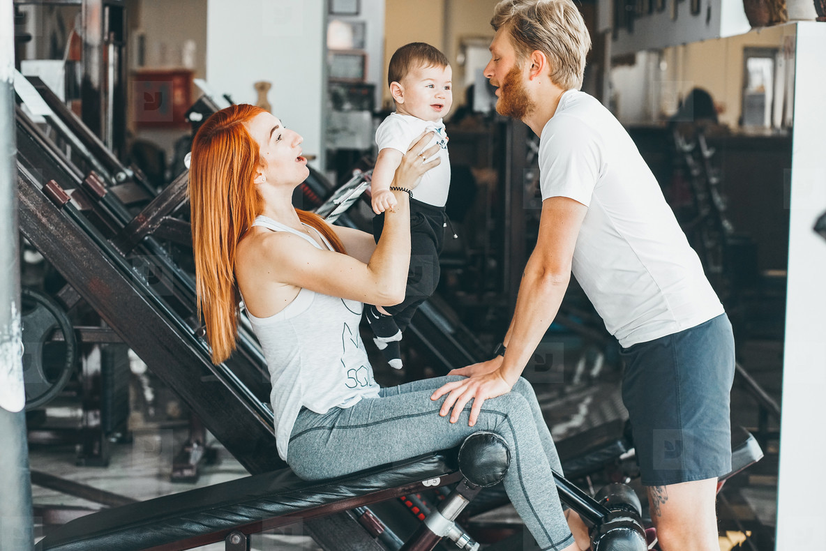 Young family with little boy in the gym